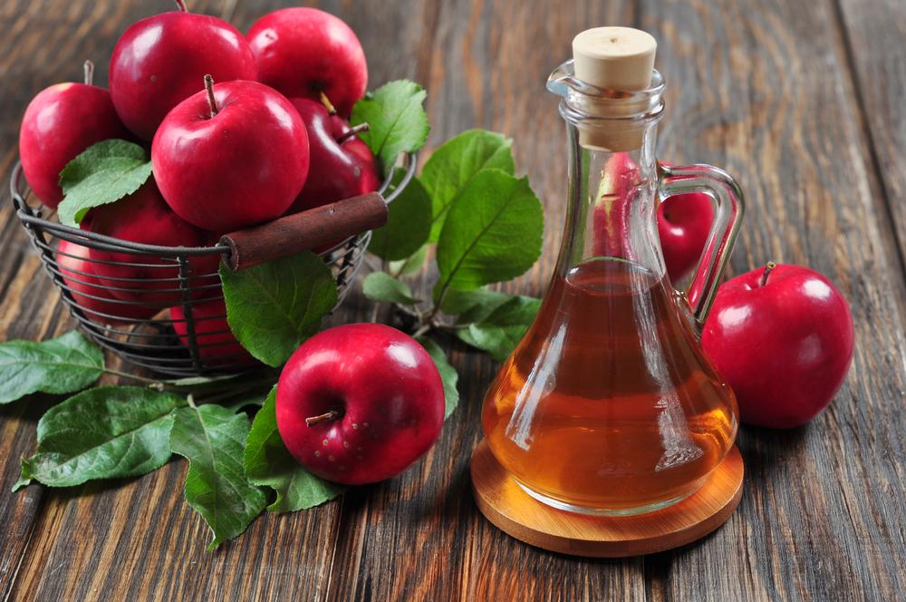 En skål med æbler ved siden af en flaske æblecidereddike